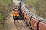 BNSF 7507 meets a wb grain train on the s curve,