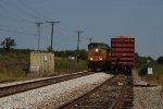 Loaded coal train waits with track equipment near white rock