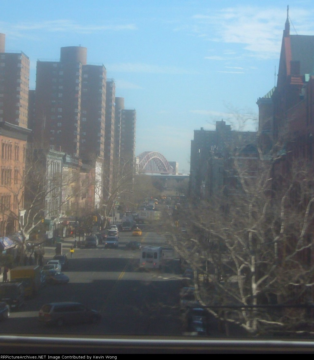 Hell Gate Bridge framed by a street in Spanish Harlem