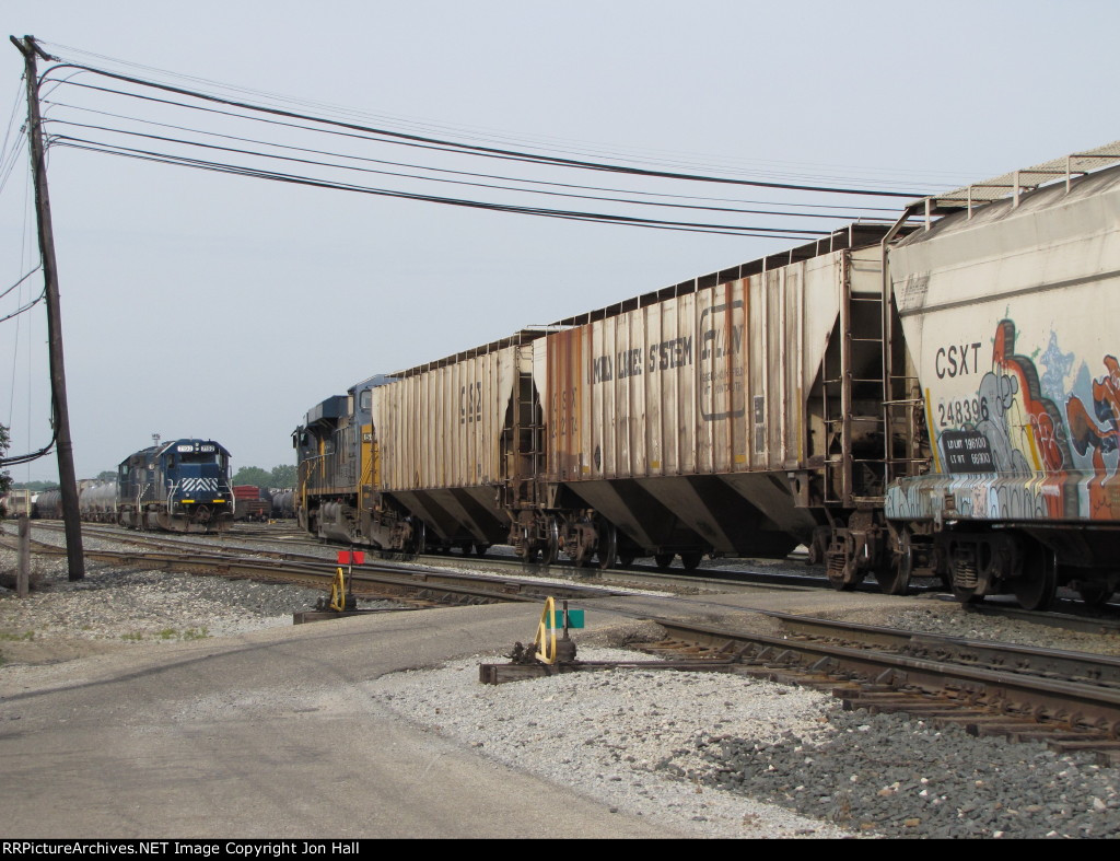 A pair of HLCX motors look on as G010-16 pulls into the yard with an empty grain train