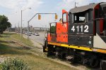 4112 starts to roll out of the road as northbound auto traffic waits for the train to clear the street running