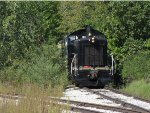 7014 shoves the old baggage car deep into the brush on what was the line to Spring Lake