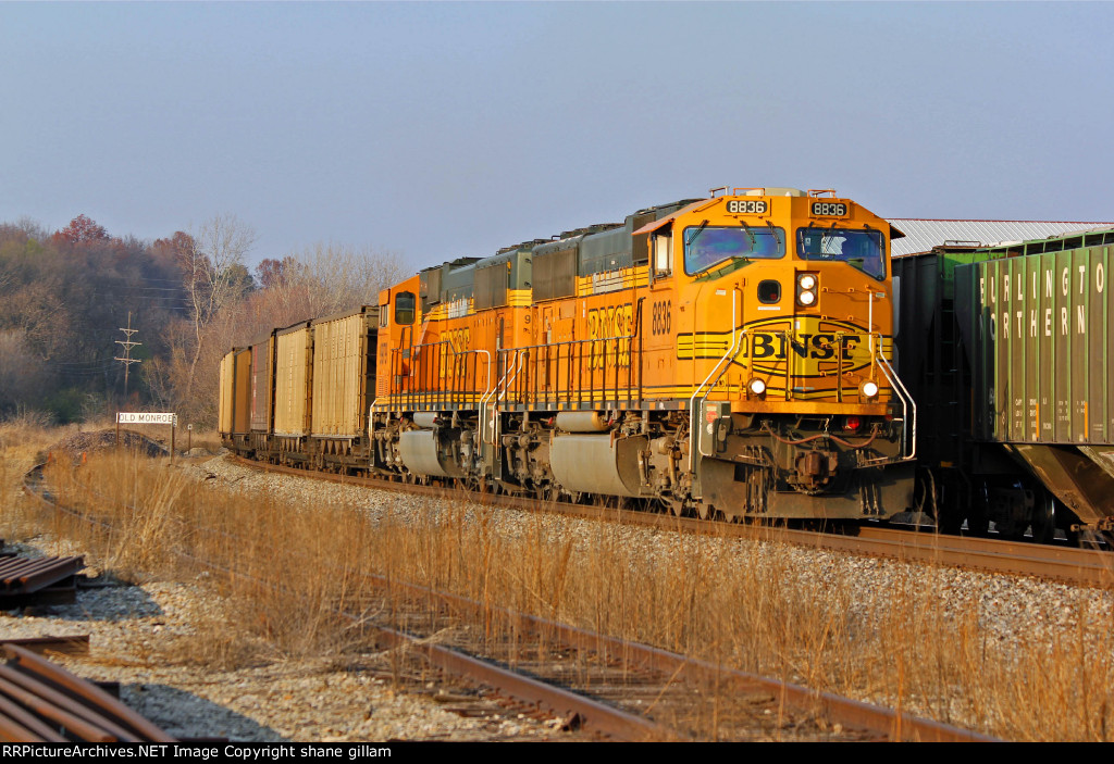 BNSF 8836 works Past a grain train in the siding.