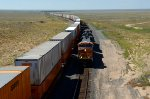 BNSF ES44C4 6961 with empty container flats passes loads at US 285 overpass east of Encino, NM.