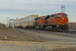 BNSF 7213 heads out of town with a JB hunt stack in tow.