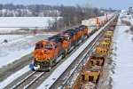 BNSF 7557 Heads Wb past a string of Baretables