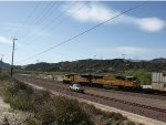 A westbound doublestack glides past a BNSF highrailer