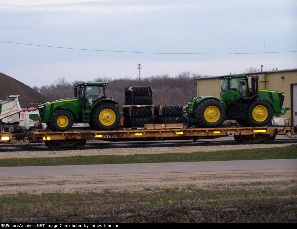 One of eight flatcars loaded w/John Deere tractors