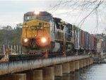 CSX locomotive 7326 crawls across the Trout River swing bridge