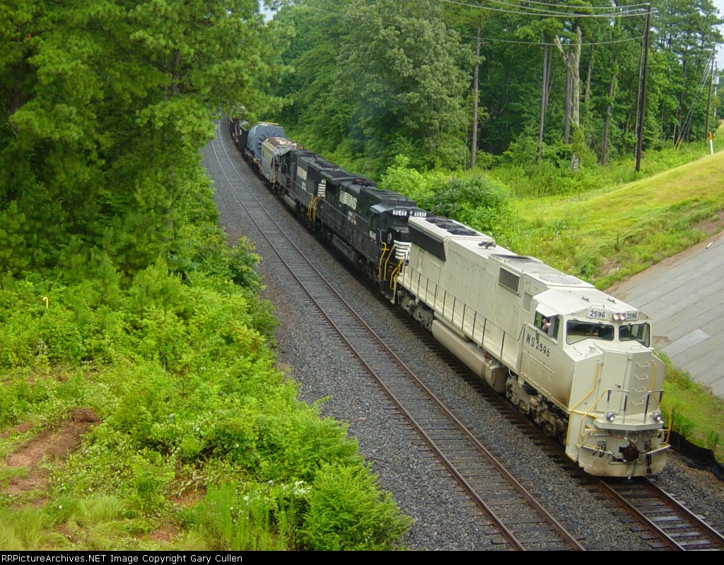 "With the engineer waving, NS train 153 heads south with high & wides & primered locomotive.  He is approaching ""Shadowbrook"""