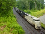 """With the engineer waving, NS train 153 heads south with high & wides & primered locomotive.  He is approaching """"Shadowbrook"""""""