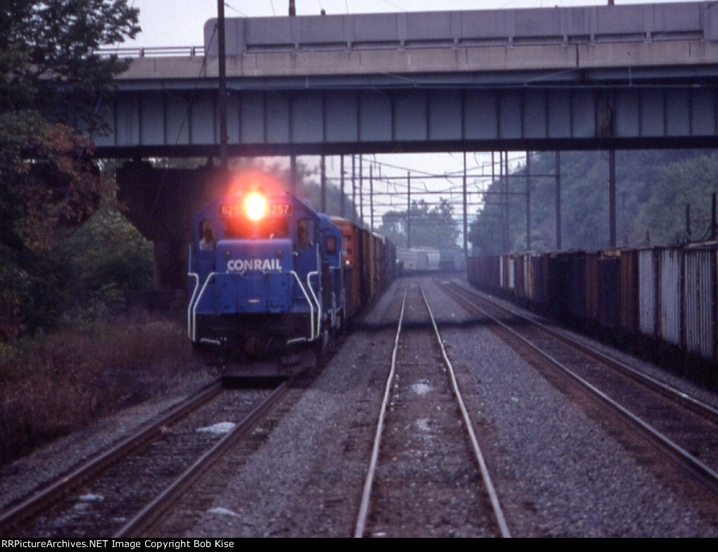 A Conrail freight barrels past the excursion train
