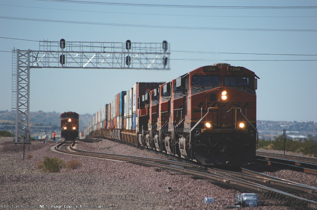Eastbound intermodal zips by an eastbound waiting to run around his train