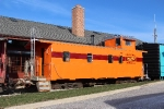 Former Santa Fe caboose looks good in it's second South Shore paint job sitting behind the new bed and breakfast