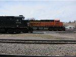 Norfolk Southern 8765 is parked near the station while BNSF 5980 leads a train by