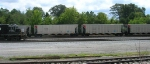 NS 5802 in yard, with TVAX coal hoppers on main line,