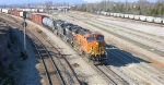 BNSF 7713 leads on mixed freight on the mainline out of town