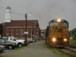 Under threatening skies, a westbound empty hopper passes the Amtrak station
