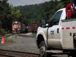 A CSX hi-rail truck takes the diamond while the southbound NECR road freight waits.