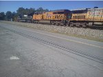 NS 8963 and UP 7497 roll past Plainville Grocery