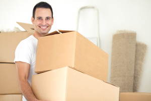 Smiling handsome man carrying packages during moving house