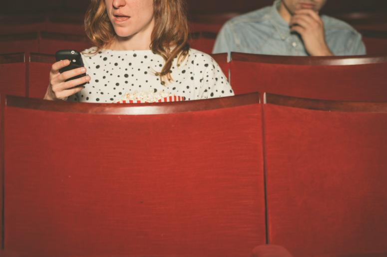 Woman using her cell phone in a theater while a young man sitting behind her looks on