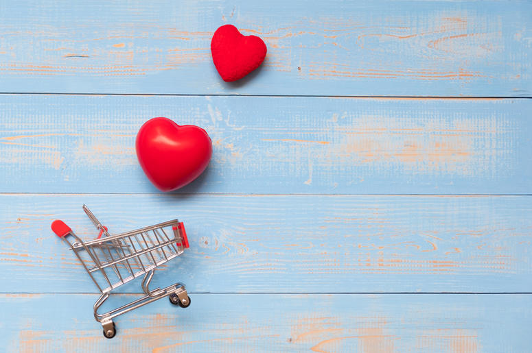 couple red heart shape with mini shopping cart on blue pastel wooden table. love, shopping and Valentine Day Concept