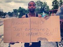 Man holding sign: Ferguson police just executed my son