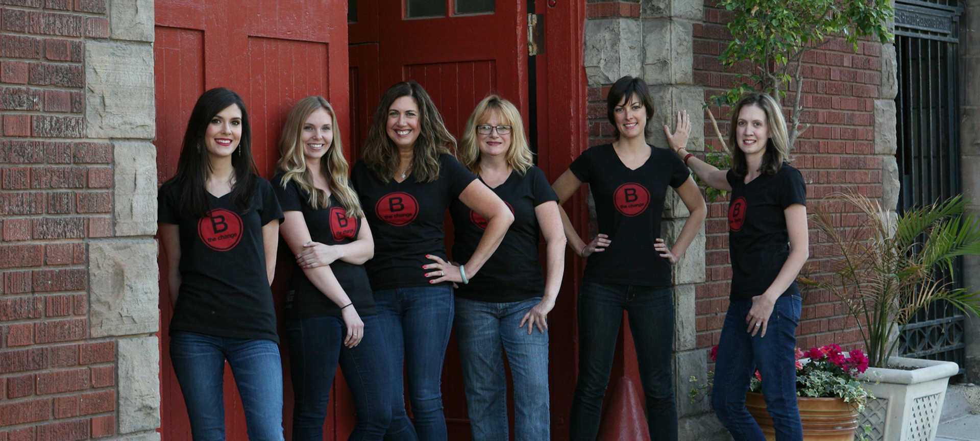 Six women in black shirts and jeans standing in front of a brick building