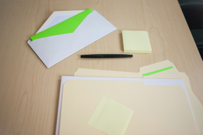 Envelope with pen and post-it note