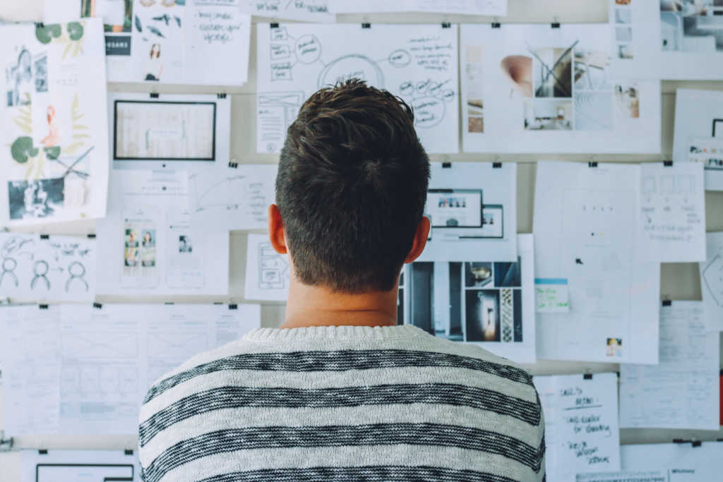Man looking at board full of graphic design