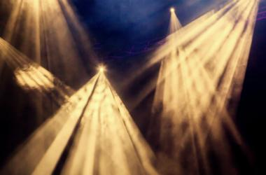 The yellow light rays from the spotlight through the smoke at the theater or concert hall.
