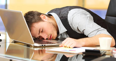man sleeping on computer