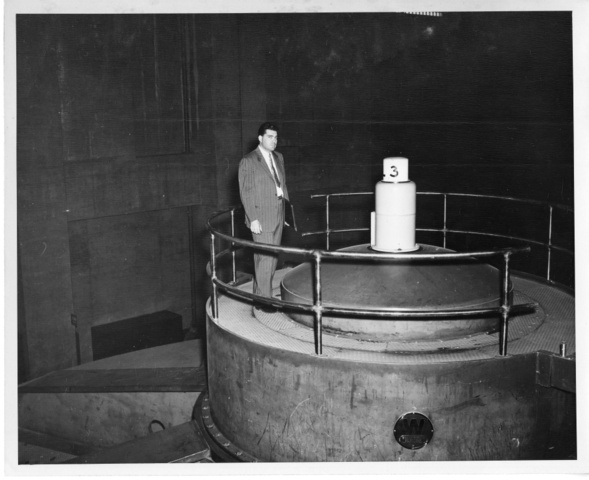 J.B. Hamlin, visiting mechanical engineer, stands atop dam generator