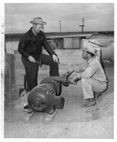 A.L. Hales and son prepare to connect a pump which will provide pressure for irrigation to the Hales farm