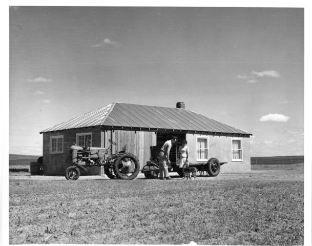 Warren Clifford and wife stand near house with adjoining machine shed on farm