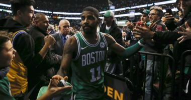 Celtics guard Kyrie Irving celebrates with fans after beating the Warriors.