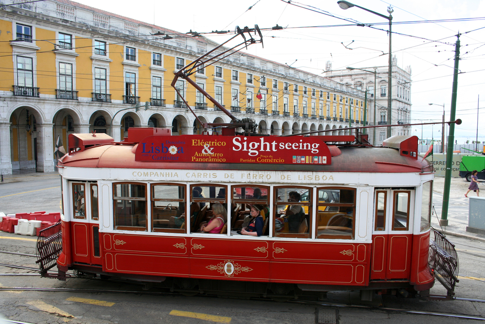 red tram goes by the street of Lisbon city center_381207991