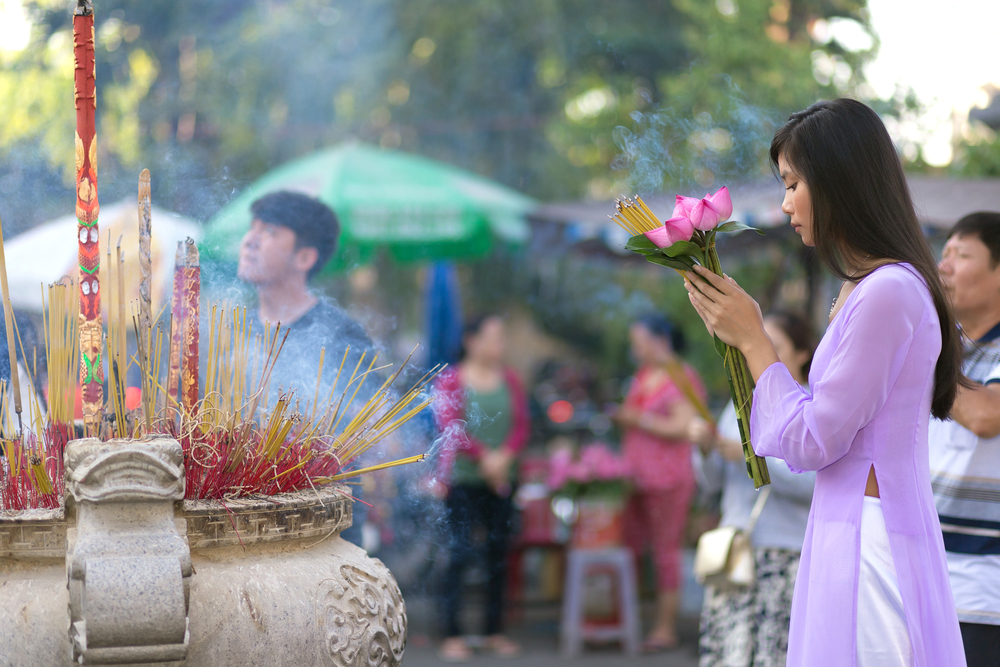 Vietnamese girl praying in Buddhist temple_265637540