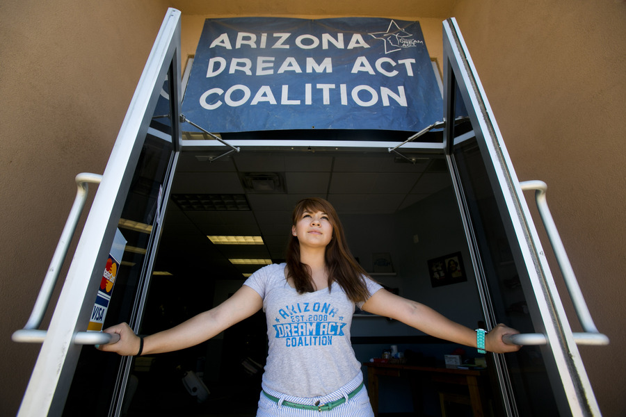 "Reyna Montoya is holding two metal doors open and looking ahead. She's wearing a gray t-shirt that says ""Arizona Dream Act Coalition"" in a sky blue font. There is a blue banner hanging over the doors that say ""Arizona Dream Act Coalition"" in white lettering with a star pattern alongside it"