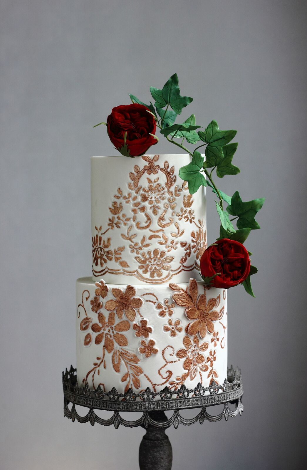 White with gold victorian wedding cake with red sugar roses