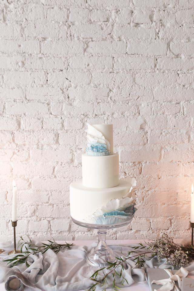 All white wedding cake with blue ombre side ruffles