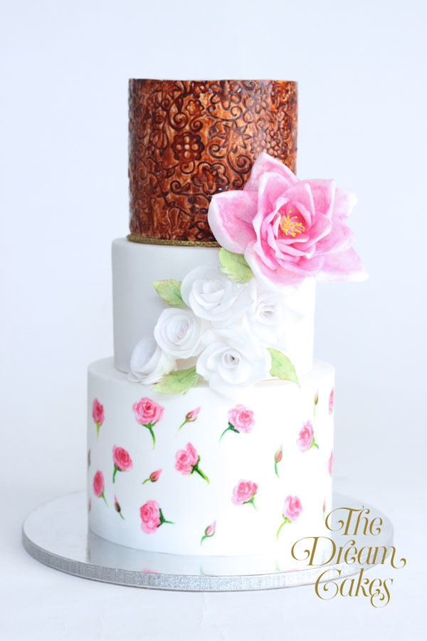 Copper and white wedding cake with handpainted pink flowers