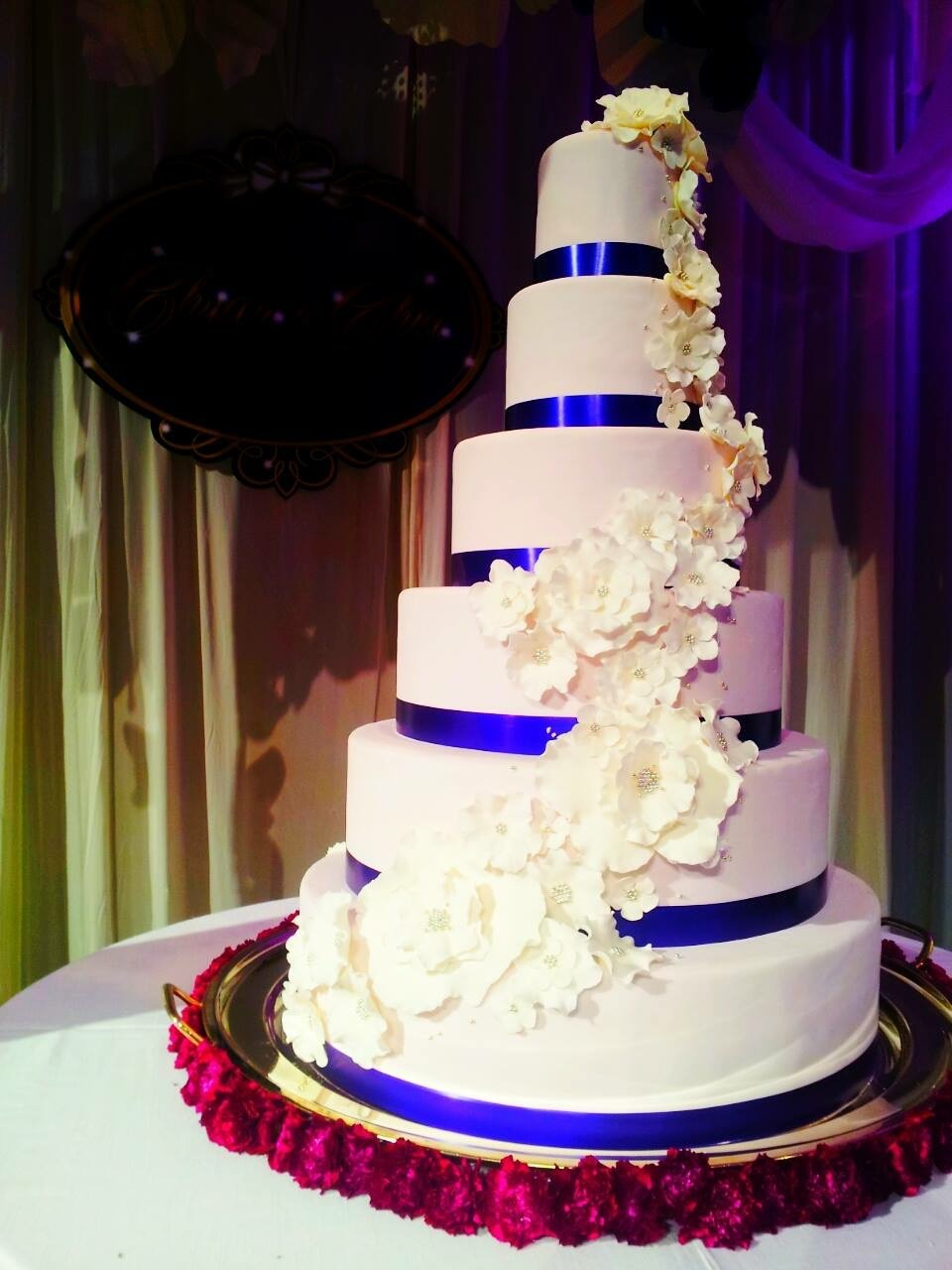 White and blue wedding cake with white cascading sugar flowers