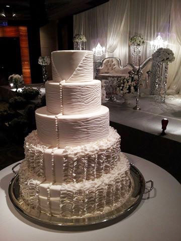 Ivory wedding cake with draping sugar pearls