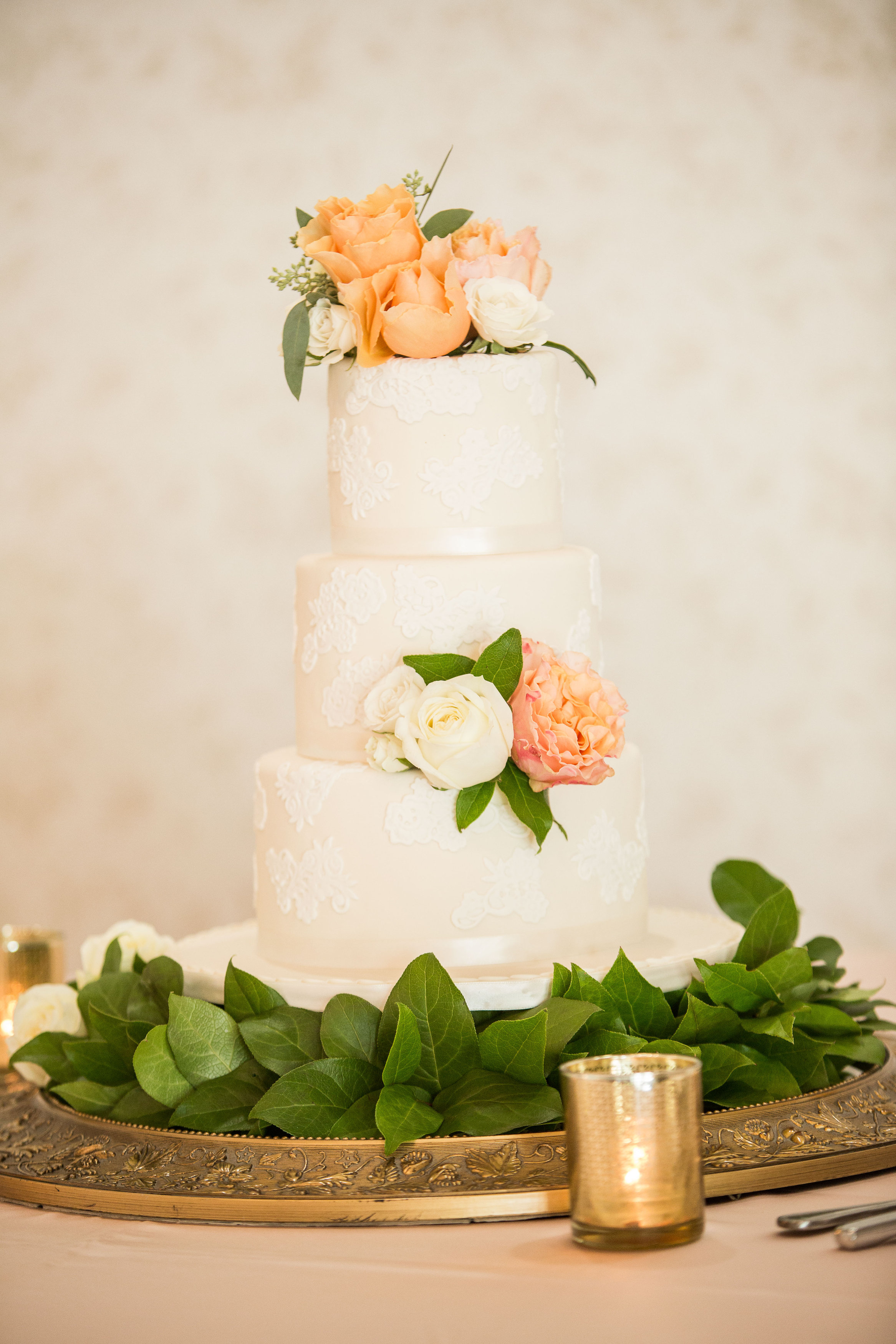 Ivory wedding cake with lace detail and peach sugar flowers