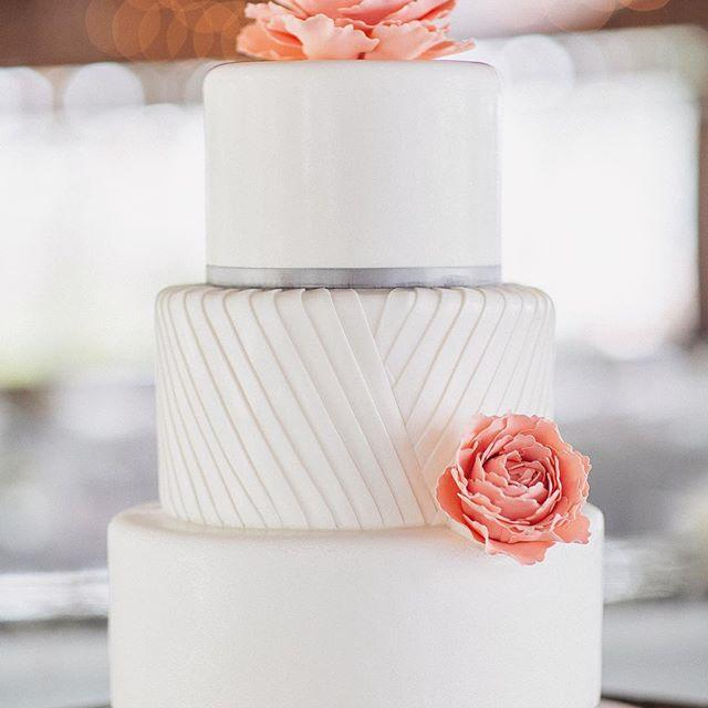 White wedding cake with pink sugar flowers