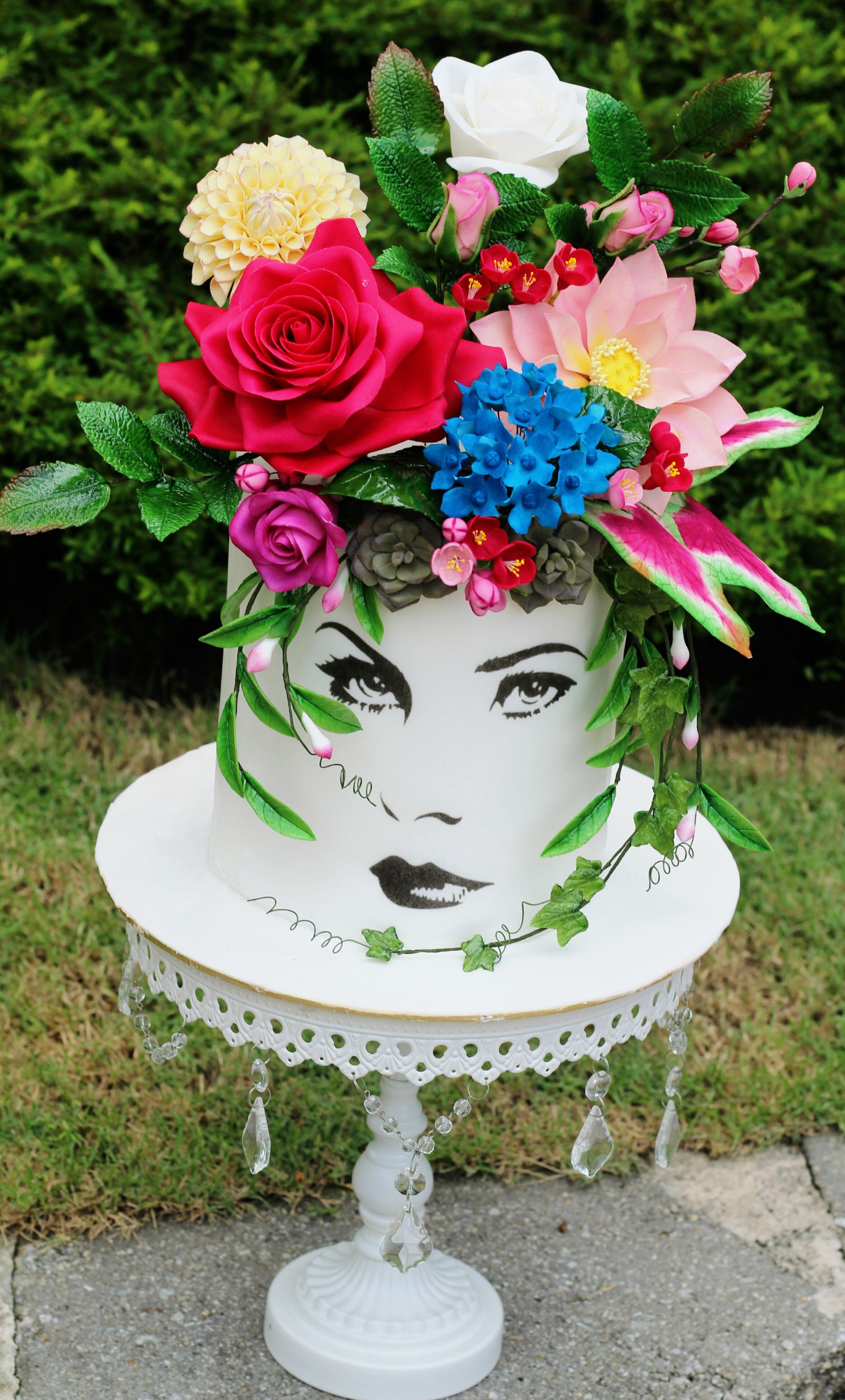 Hand painted face cake with sugar flower topper