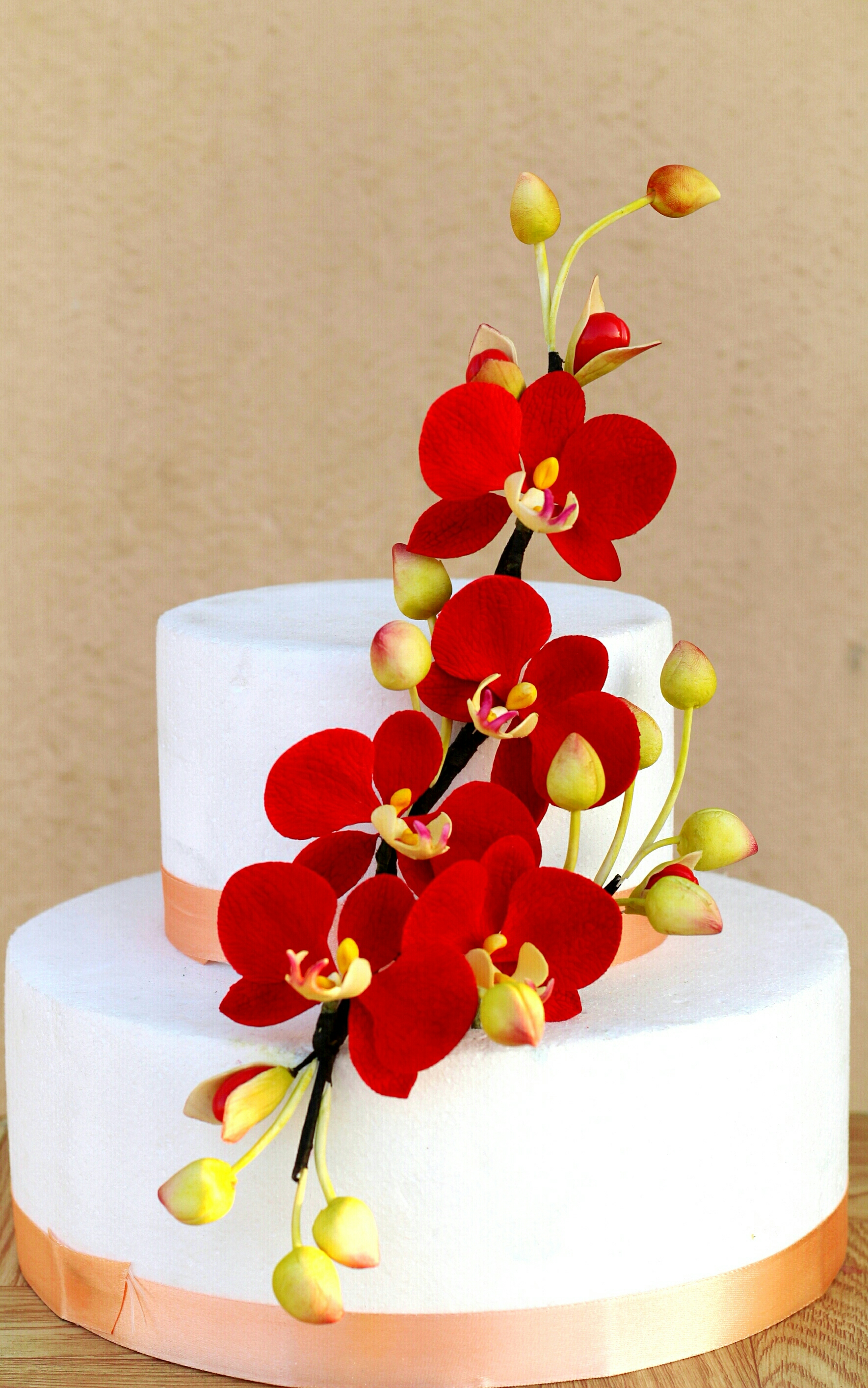 White wedding cake with red sugar lilies