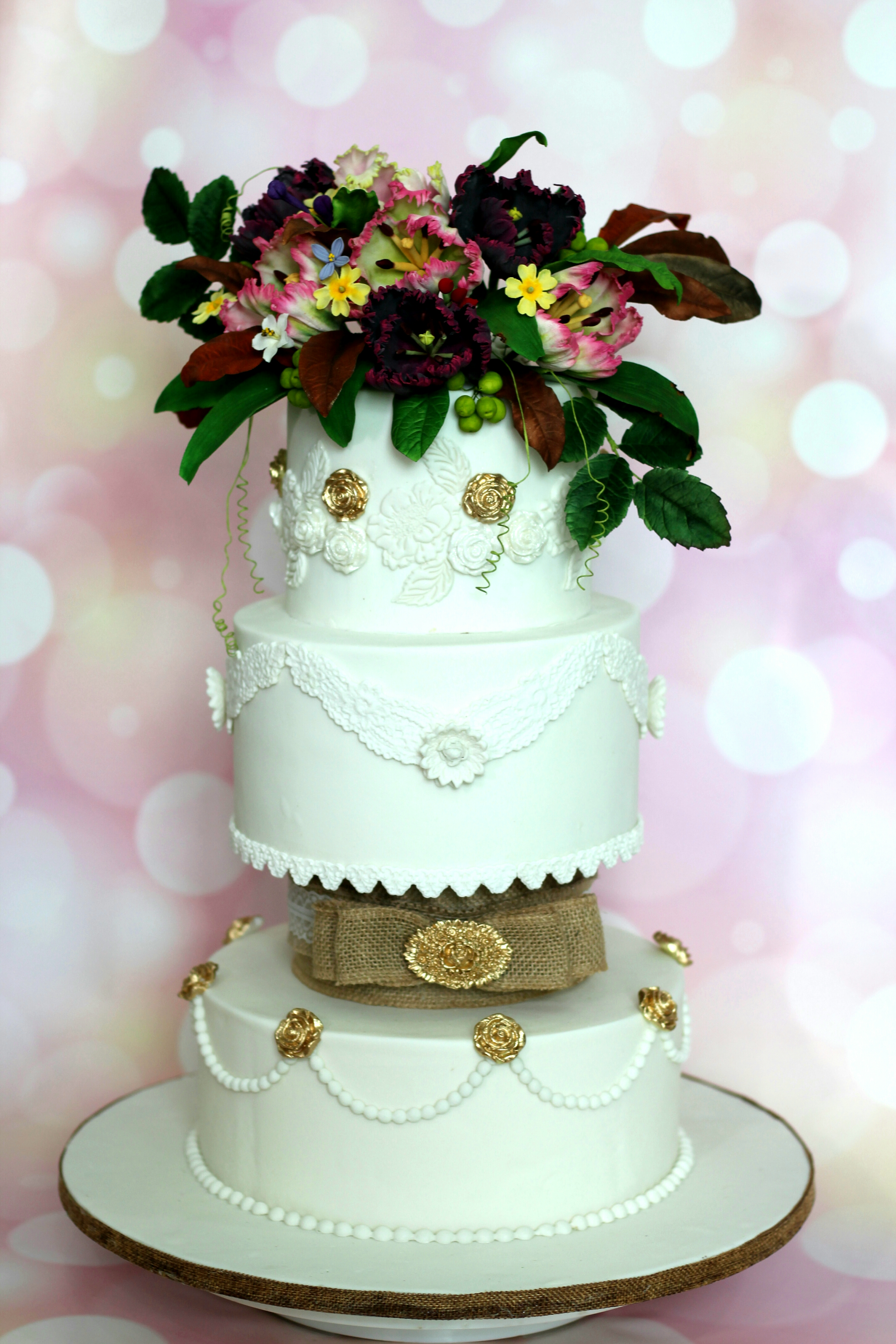 White ornate wedding cake with dark sugar flowers on top